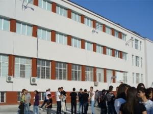 Деца гледат арести през оградата на училището си