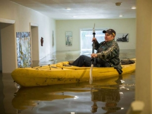Заради наводнение: Жена кара каяк в собствения си дом СНИМКИ