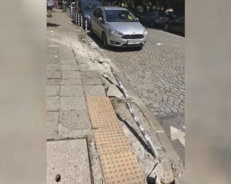 Жена качи колата на тротоара, помете знаци и колчета пред училище