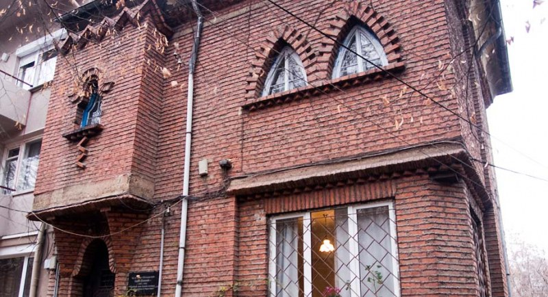 Къщата на Сирак Скитник, построена по съновидения, омайва с червени тухли и малки прозорчета